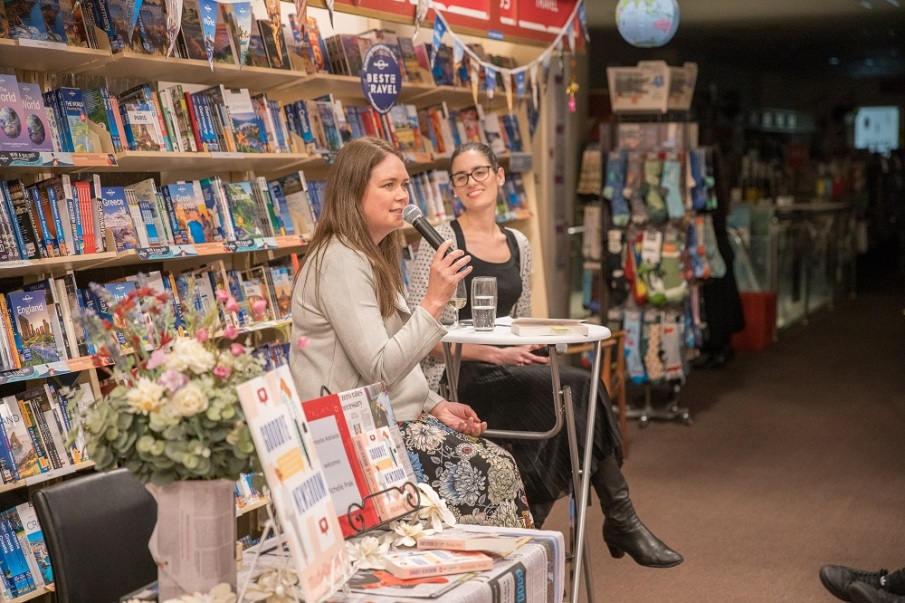 Michelle Prak at bookstore launch, holding microphone